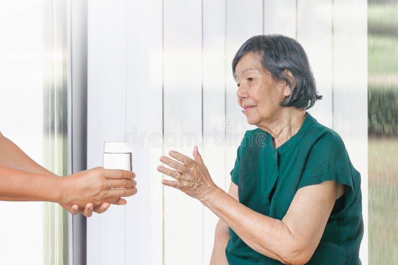 Starsza kobieta dostaje szk?o woda od opiekunu obrazy royalty free