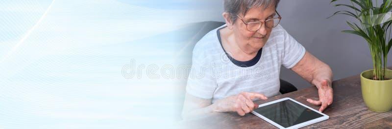 Starsza kobieta i nowe technologie sztandar panoramiczny obrazy royalty free