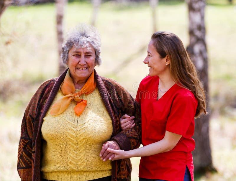 Starsza kobieta i potomstwo opiekun obraz royalty free