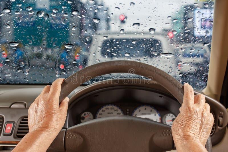 Starsza kobieta jedzie samochód w mieście wolno, deszczowy dzień obraz royalty free