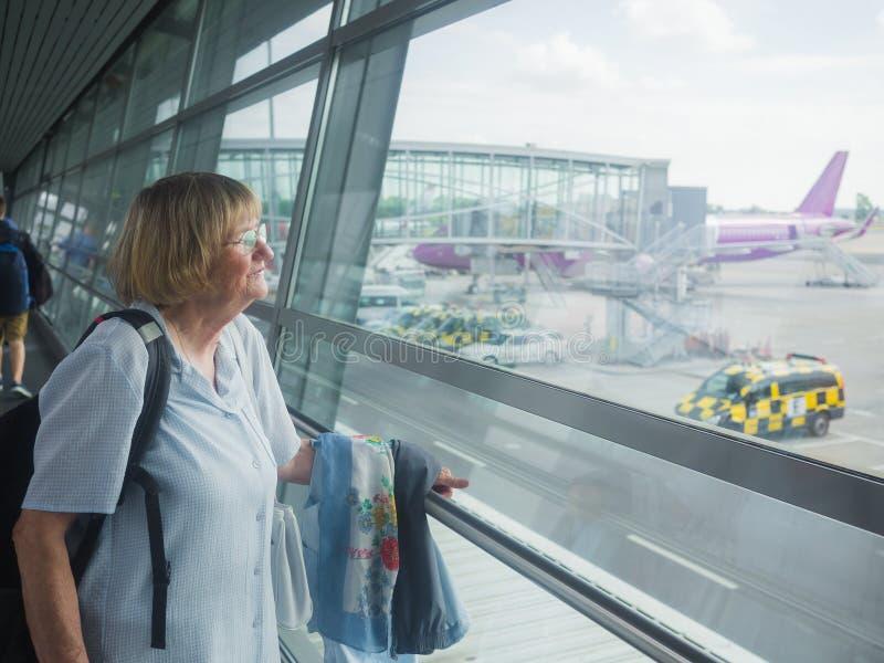 Starsza kobieta jest przyglądająca przez okno przy lotniskiem fotografia royalty free