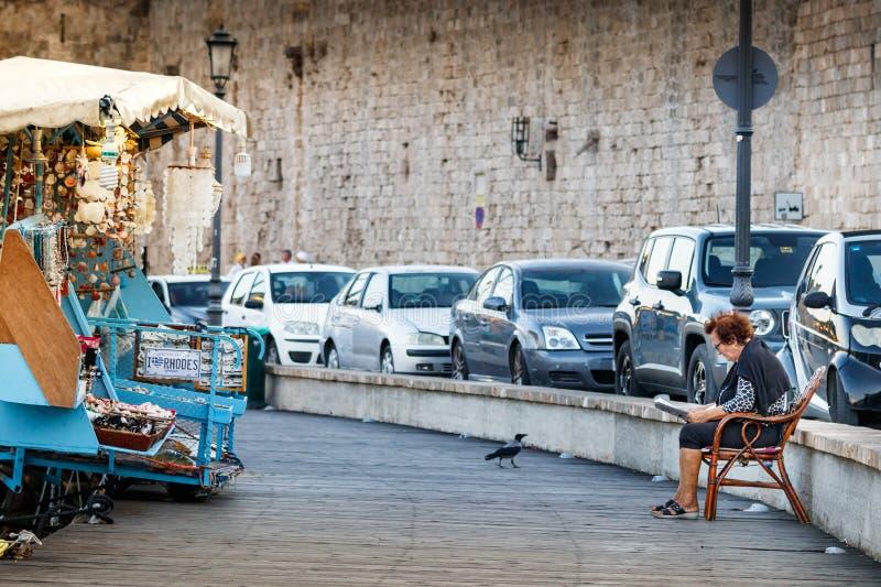 Starsza kobieta jest ubranym eyeglasses, czyta gazetowego obsiadanie na krześle na zewnątrz nabrzeża Rhodes, Grecja fotografia royalty free