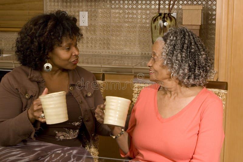 Starsza kobieta ma kawę z jej córką obrazy stock