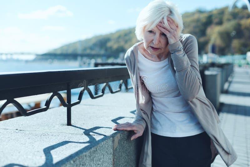 Starsza kobieta ma zawroty głowy outdoors fotografia royalty free