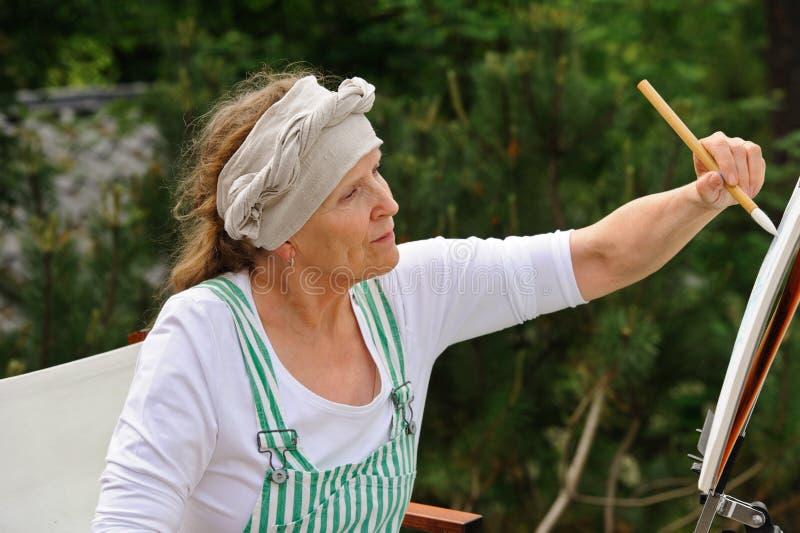 Starsza kobieta maluje outdoors zdjęcie stock