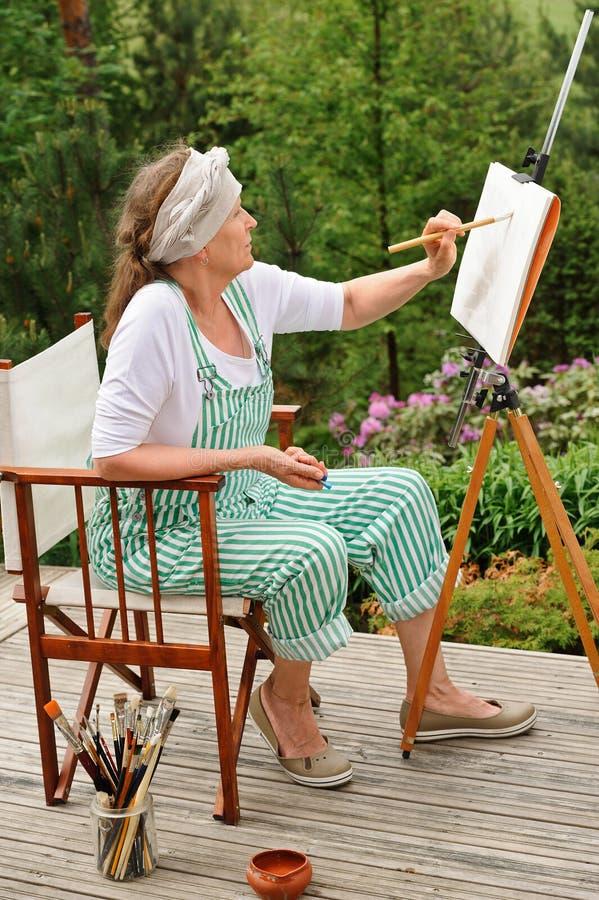 Starsza kobieta maluje outdoors zdjęcie royalty free