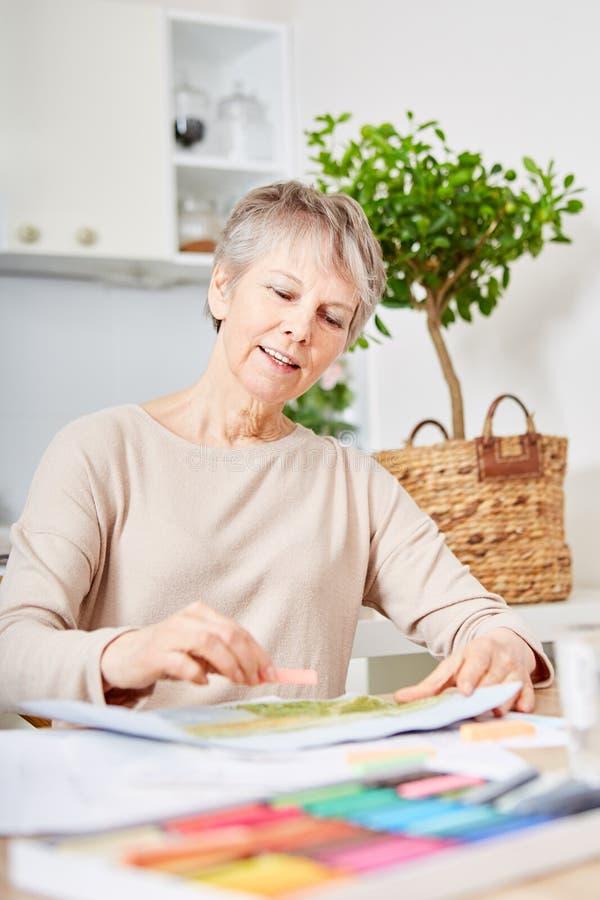 Starsza kobieta maluje w domu z demencją zdjęcia royalty free