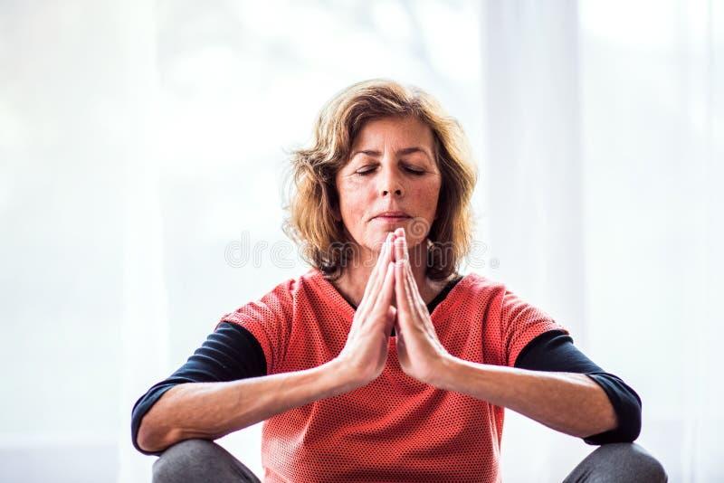 Starsza kobieta medytuje w domu zdjęcie stock