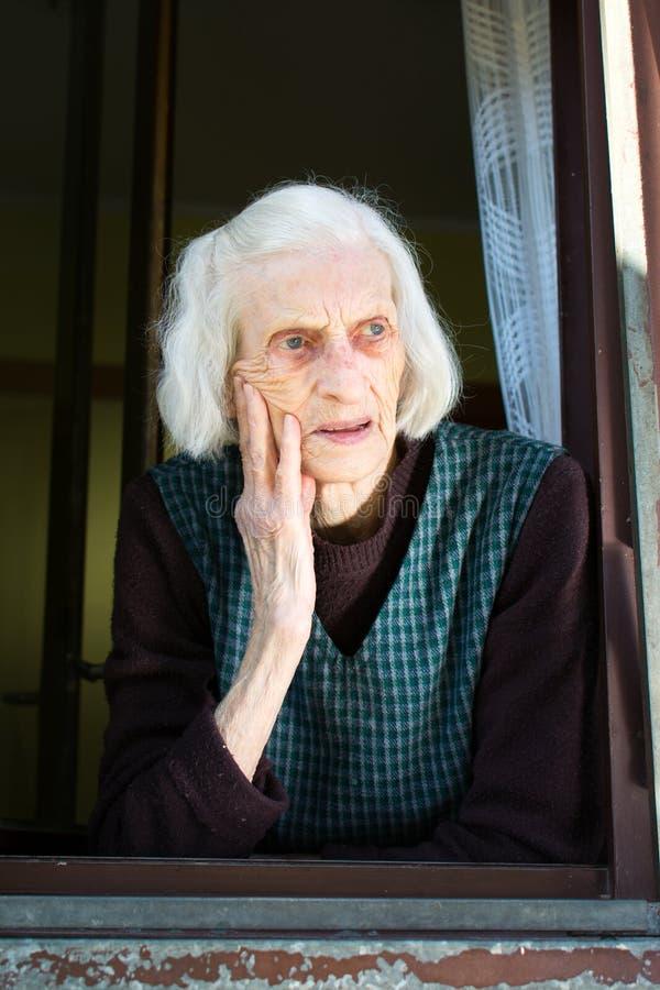Starsza kobieta na domowym okno obrazy royalty free