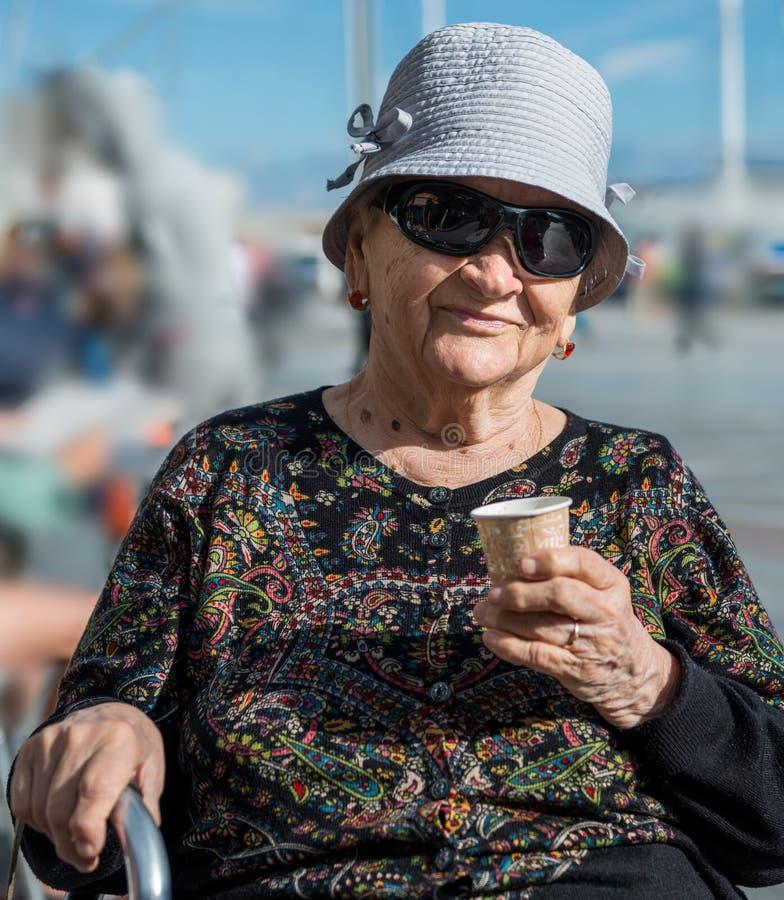 Starsza kobieta na kapeluszu ma filiżanka kawy obraz royalty free