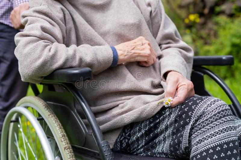 Starsza kobieta na wózku inwalidzkim z pomocą medyczną obraz stock