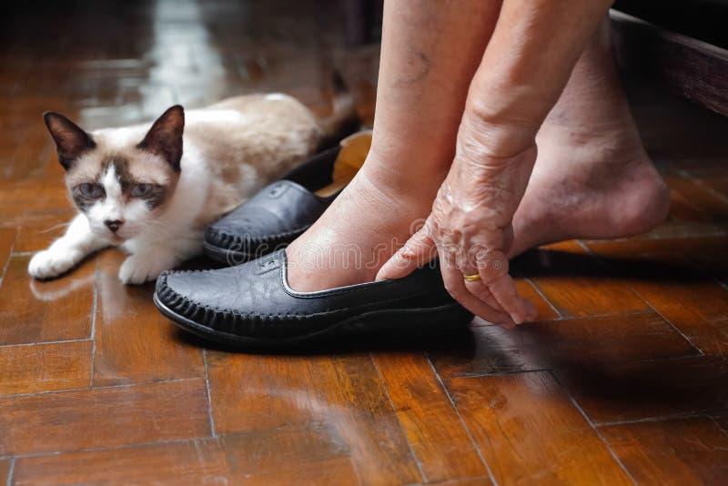 Starsza kobieta nabrzmiewająca cieki stawia na butach obraz stock