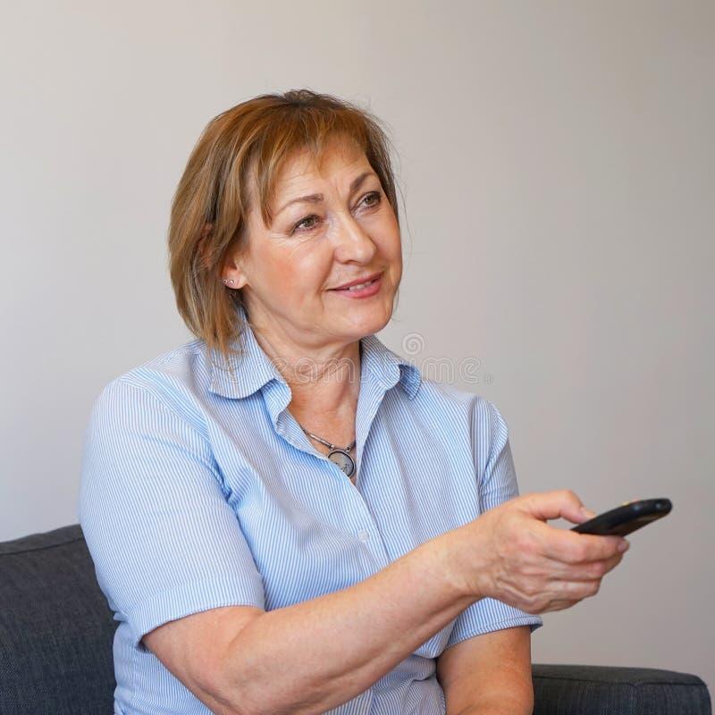 Starsza kobieta ogląda tv na kanapie obrazy royalty free