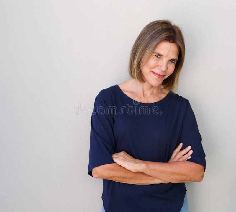 Starsza kobieta ono uśmiecha się przeciw szarości ścianie fotografia royalty free