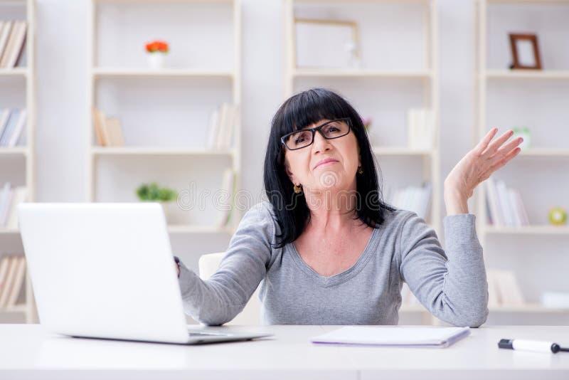 Starsza kobieta ono zmaga się przy komputerem zdjęcia stock