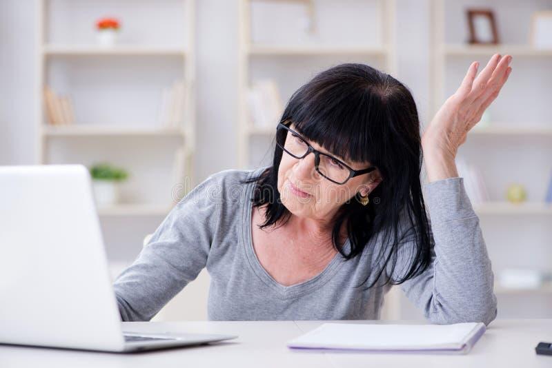 Starsza kobieta ono zmaga się przy komputerem obraz royalty free
