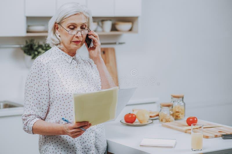 Starsza kobieta opowiada na telefonie podczas gdy robić posiłkowi salowy obraz royalty free