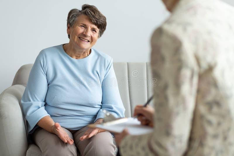 Starsza kobieta opowiada pieniężny advisor o pożyczce obraz stock