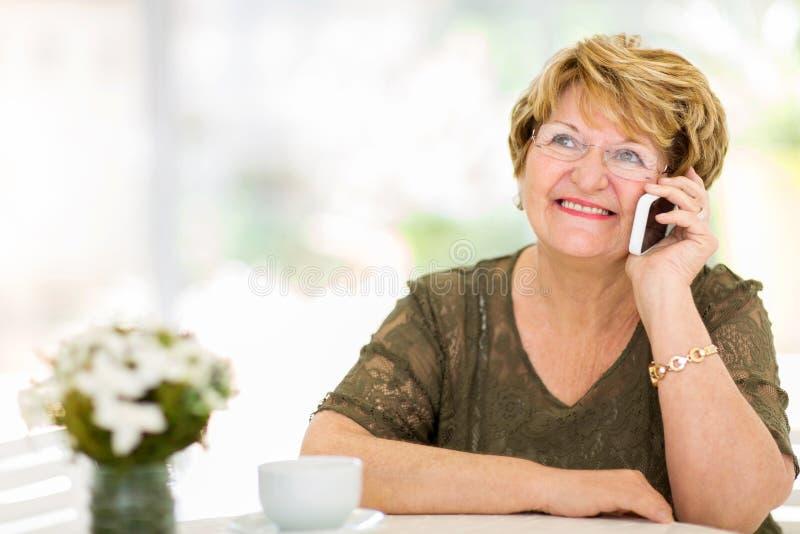 Starsza kobieta opowiada telefon zdjęcie stock