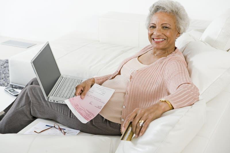 Starsza kobieta Płaci rachunki Online fotografia royalty free
