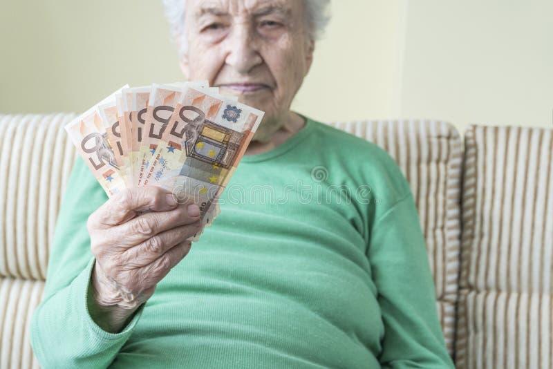 Starsza kobieta patrząca na banknoty euro w dłoni fotografia royalty free