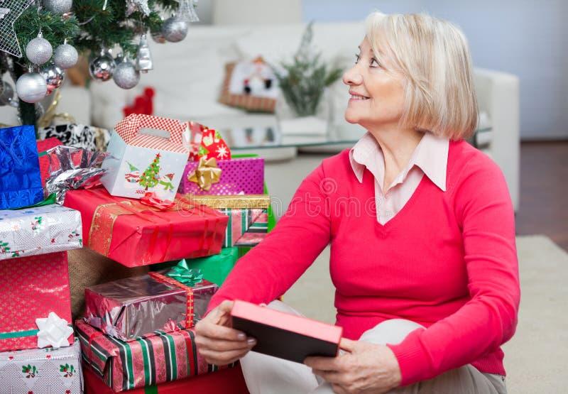 Starsza kobieta Patrzeje Daleko od Z Bożenarodzeniową teraźniejszością zdjęcia royalty free