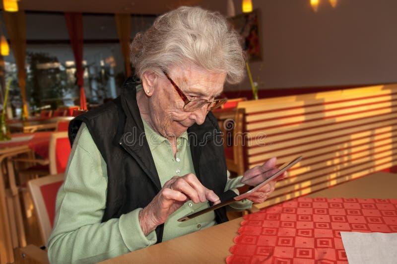 Starsza kobieta patrzeje ekran pastylka komputer obrazy stock