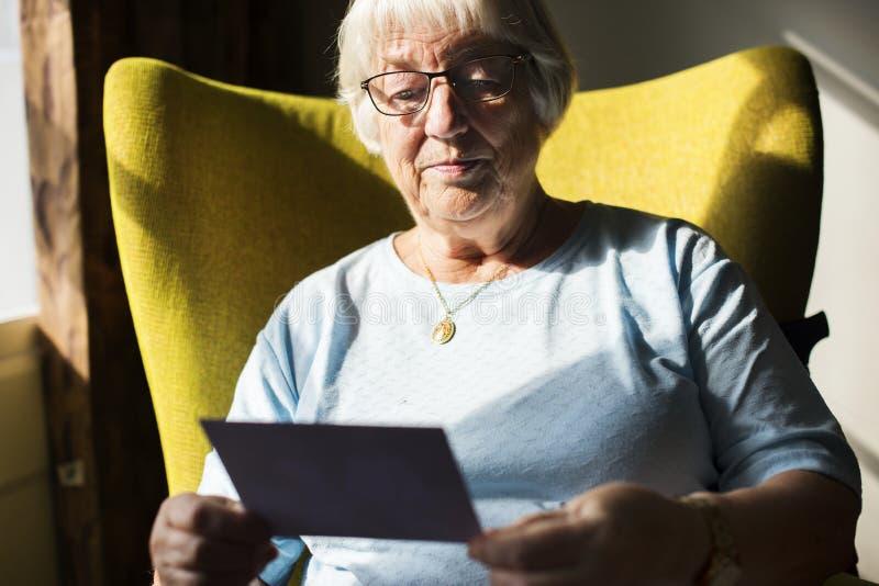 Starsza kobieta patrzeje fotografię zdjęcia stock