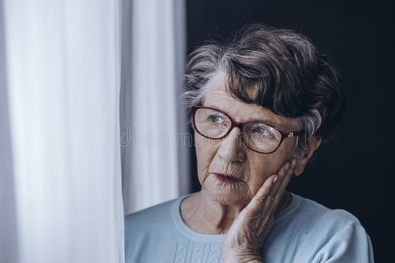 Starsza kobieta patrzeje przez okno zdjęcie stock