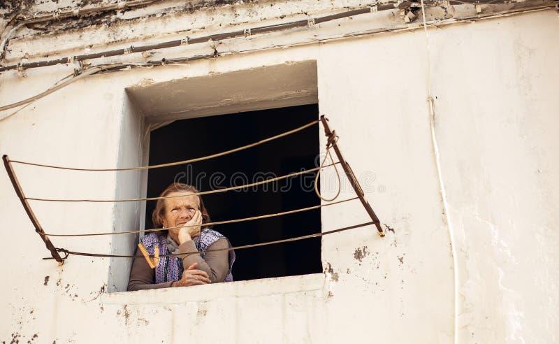 Starsza kobieta patrzeje przez okno w Bari zdjęcia royalty free