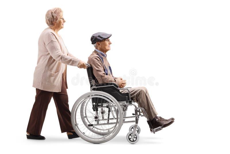 Starsza kobieta pcha starszego mężczyzny w wózku inwalidzkim zdjęcia royalty free