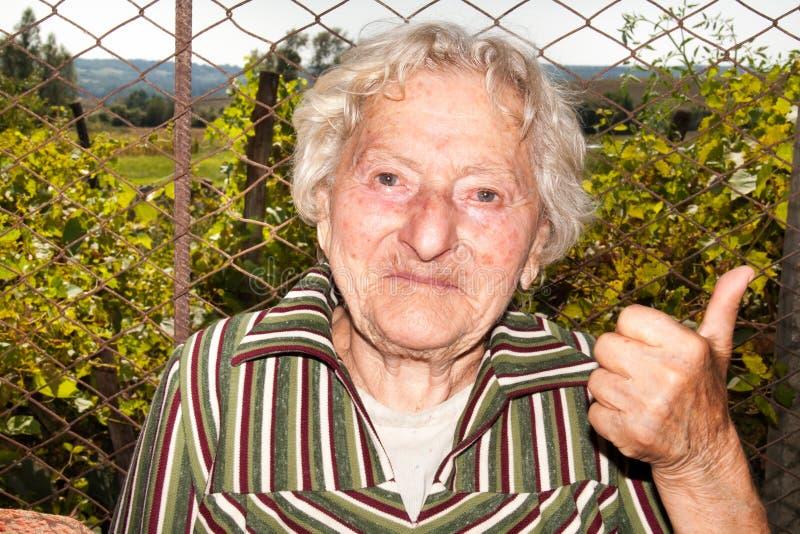 Starsza kobieta pokazuje kciuk w górę natury w obraz royalty free