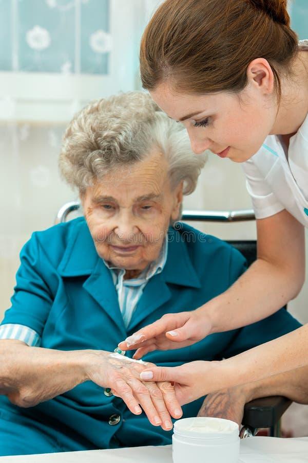 Starsza kobieta pomaga pielęgniarką w domu zdjęcia royalty free