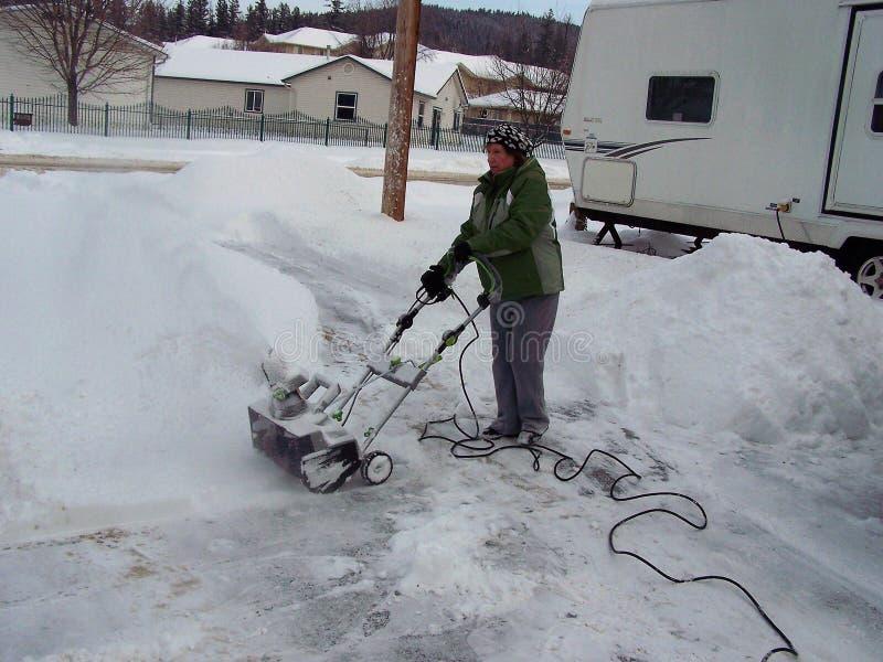 Starsza kobieta pracuje śnieżną dmuchawę fotografia stock