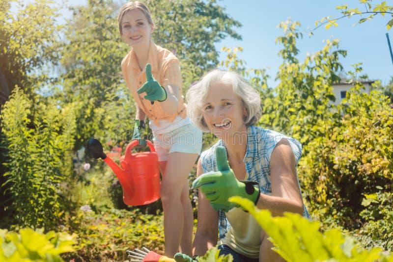 Starsza kobieta pracuje w warzywach podczas gdy córka nawadnia ogród obrazy stock
