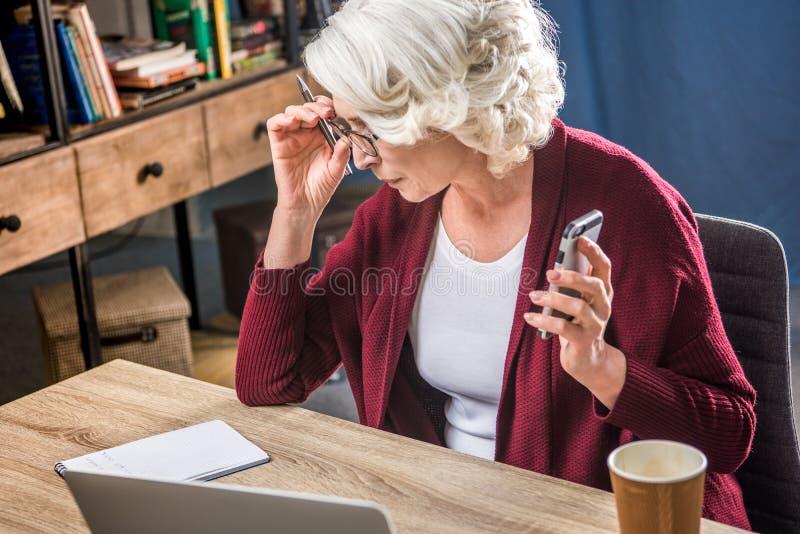 Starsza kobieta przystosowywa eyeglasses zdjęcia royalty free