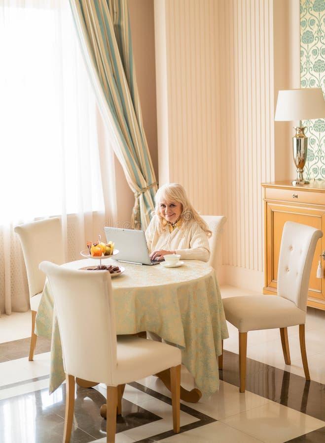 Starsza kobieta relaksuje w domu siedzieć przy stołem przy laptopem zdjęcia stock