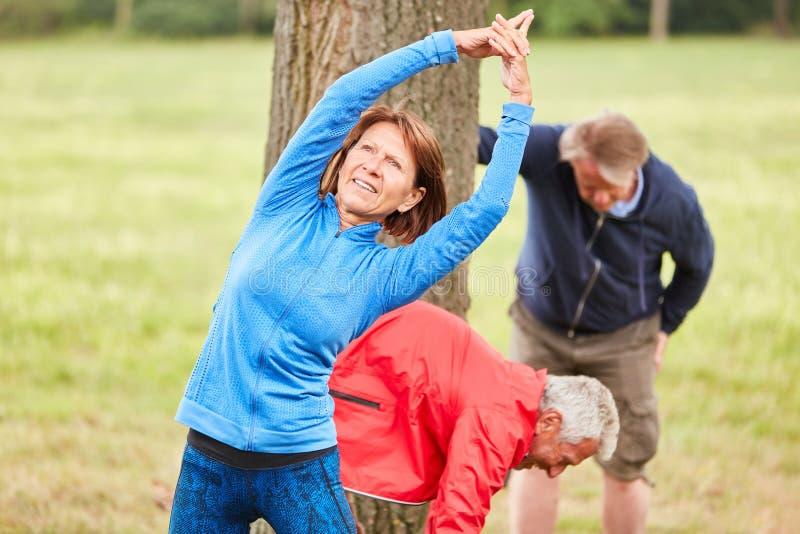 Starsza kobieta robi rozciąganiu grzać w górę zdjęcia royalty free