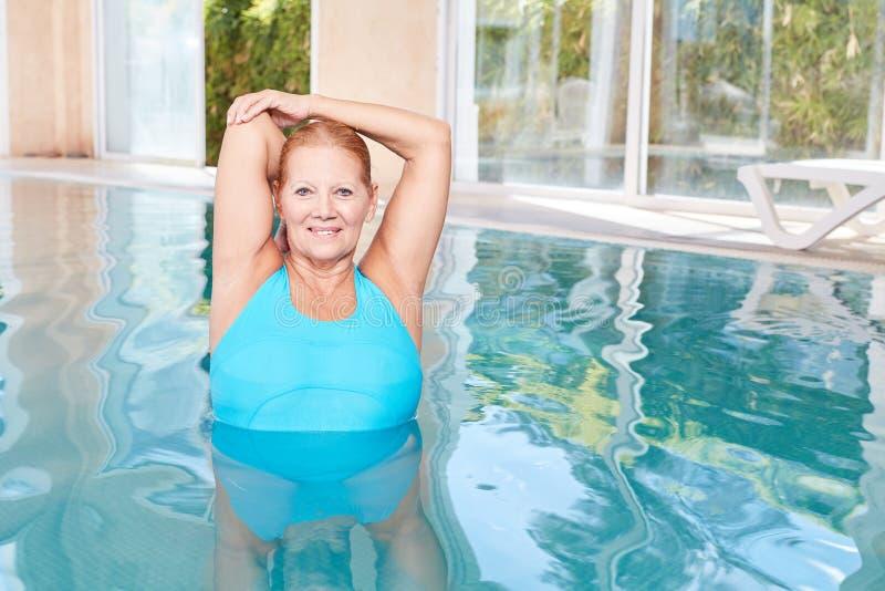 Starsza kobieta robi zdrowemu rozciągania ćwiczeniu podczas wodnych aerobików fotografia stock