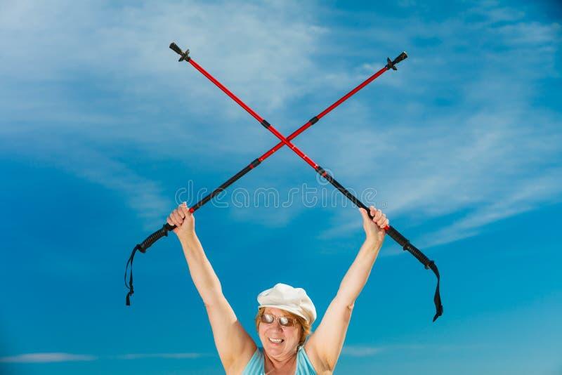 Starsza kobieta rozgrzewkowa z chodzącymi słupami up zdjęcie stock