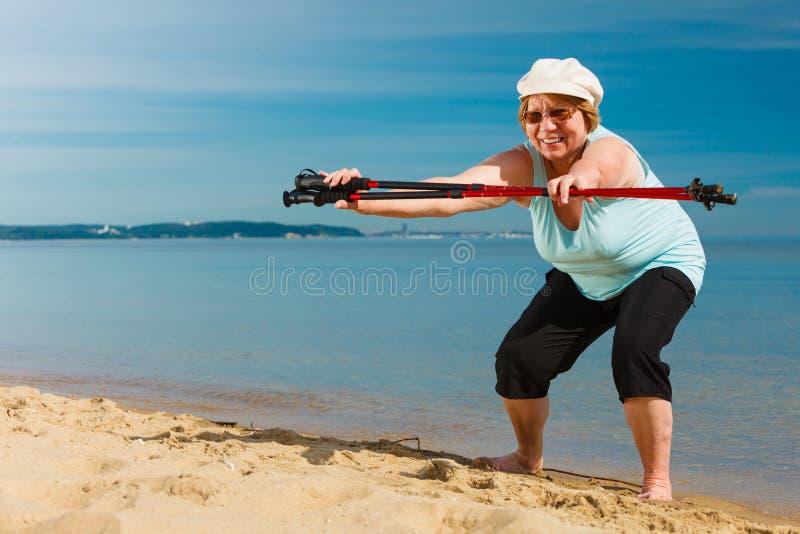 Starsza kobieta rozgrzewkowa z chodzącymi słupami up fotografia royalty free