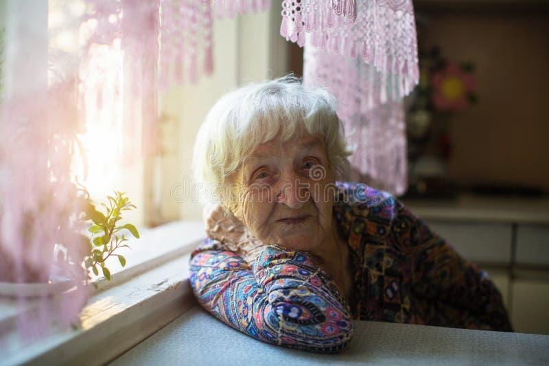 Starsza kobieta siedząca przy stole w domu obrazy stock