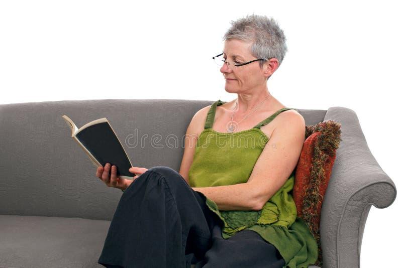 Starsza kobieta siedzi na kanapie i czyta książkę zdjęcia royalty free