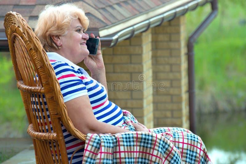 Starsza kobieta siedzi w łozinowym kołysa krześle i opowiadać na telefonie komórkowym dobrej komunikacji Relaksuje w dom na wsi zdjęcia royalty free