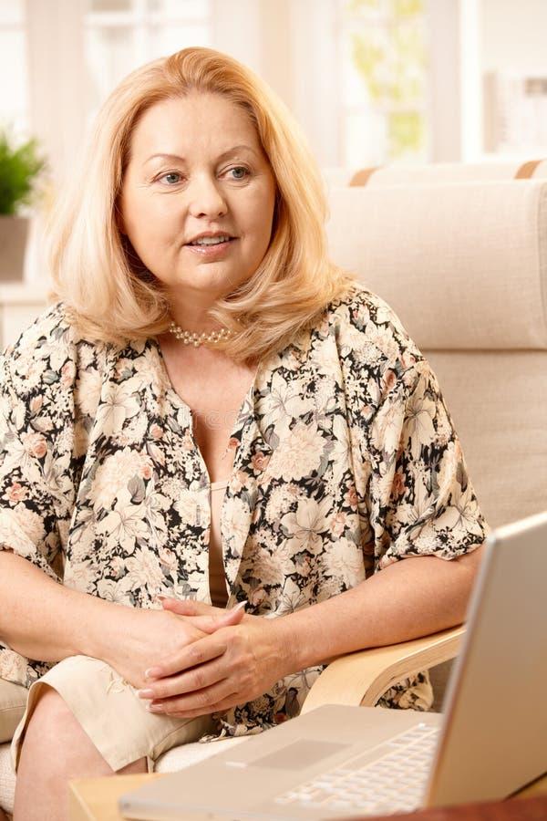 Starsza kobieta z komputerem w domu obrazy stock