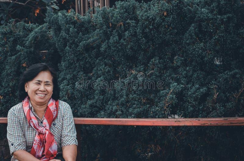 Starsza kobieta siedzi w jawnym parku zdjęcia stock