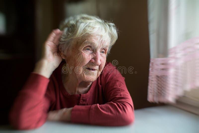Starsza kobieta stawia jej rękę jej ucho, rusza się w plamie obraz stock