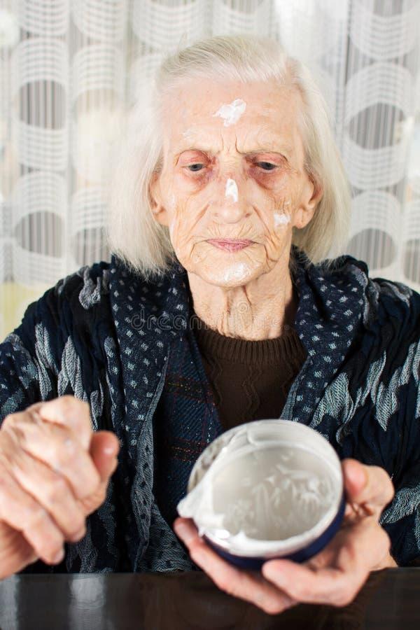 Starsza kobieta stosuje twarzy śmietankę fotografia royalty free