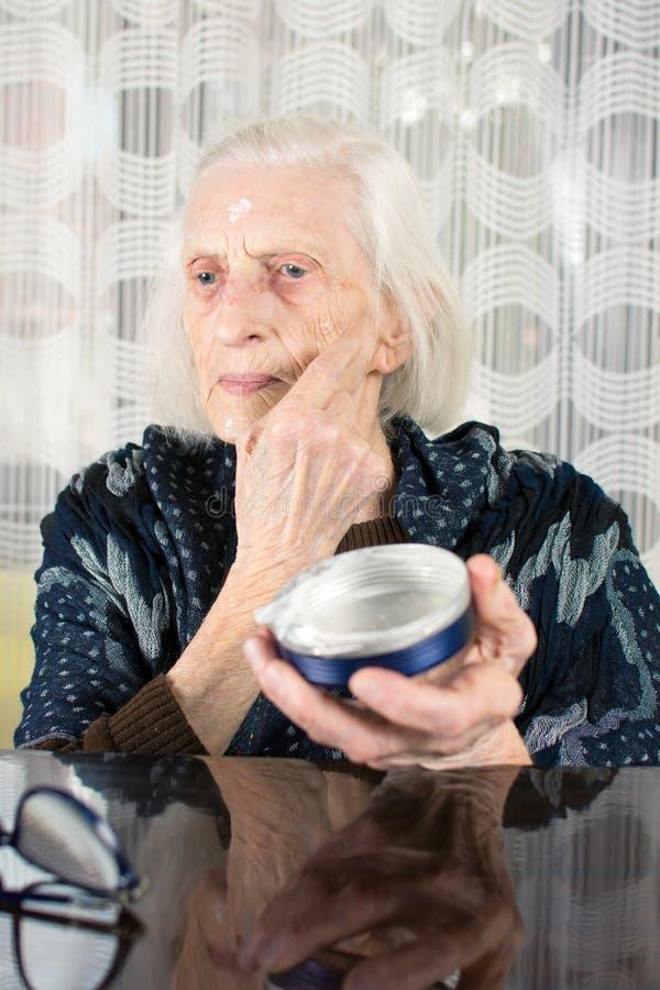 Starsza kobieta stosuje twarzy śmietankę fotografia stock