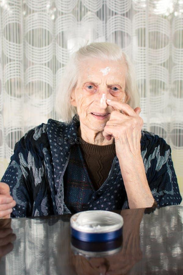 Starsza kobieta stosuje twarzy śmietankę zdjęcie royalty free